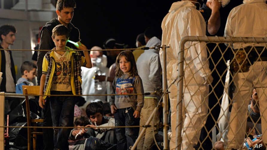 """FILE - Migrants wait to disembark from the Italian Navy Ship """"Grecale"""" at Pozzallo harbour, Sicily, May 13, 2014."""