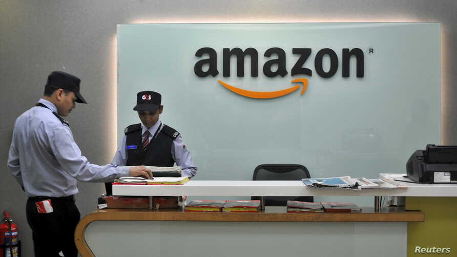 FILE - Security guards stand at the reception desk of the Amazon India office in Bengaluru, India, Aug. 14, 2015.