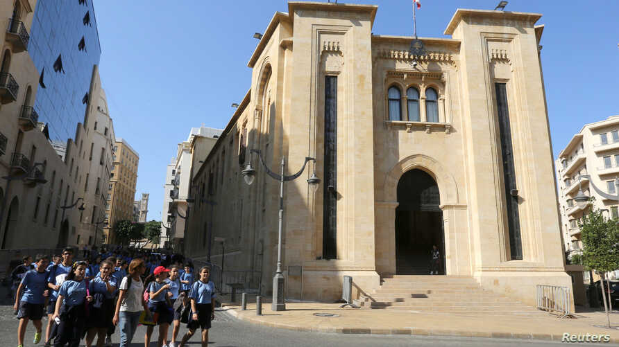 FILE - Students walk outside the parliament building in downtown Beirut, Lebanon.