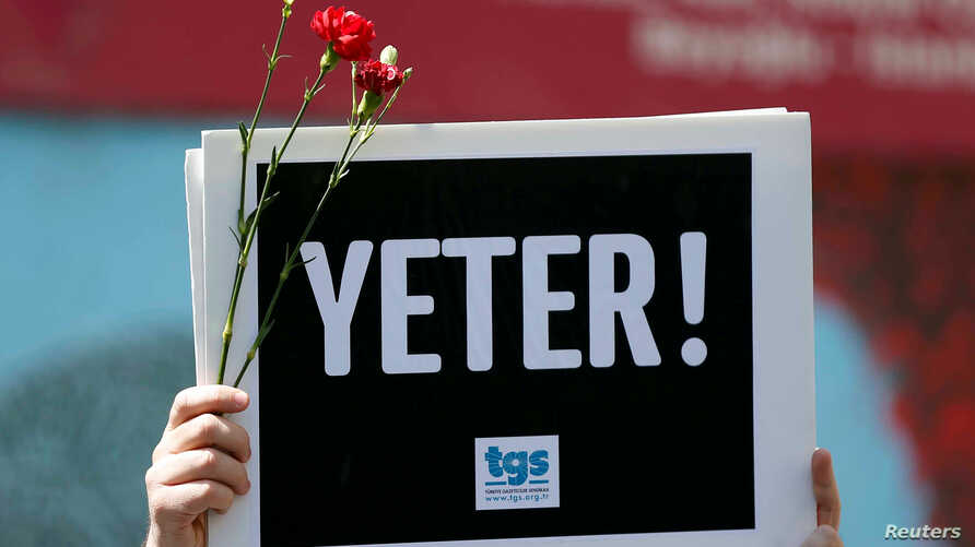 "A member of the Journalists Union of Turkey holds a placard reading ""Enough!"" during a demonstration to mark World Press Freedom Day in central Istanbul, May 3, 2017."