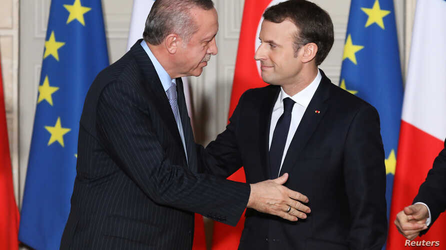 French President Emmanuel Macron greets Turkish President Recep Tayyip Erdogan during a joint news conference at the Elysee Palace in Paris, France, Jan. 5, 2018.