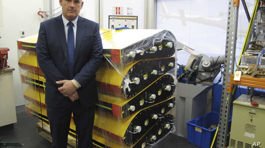Peter Foley, Australian Transport Safety Bureau director of Malaysian Flight 370 search operations, stands beside a stack of replica wing flaps, Aug. 18, 2016, at the bureau's headquarters in Canberra, Australia.