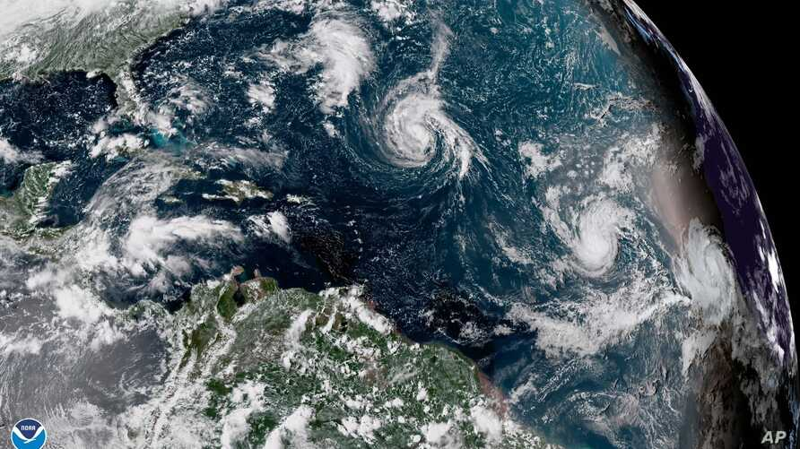 This enhanced satellite image made available by NOAA shows Tropical Storm Florence, center, in the Atlantic Ocean, at midafternoon EDT, Sept. 8, 2018.