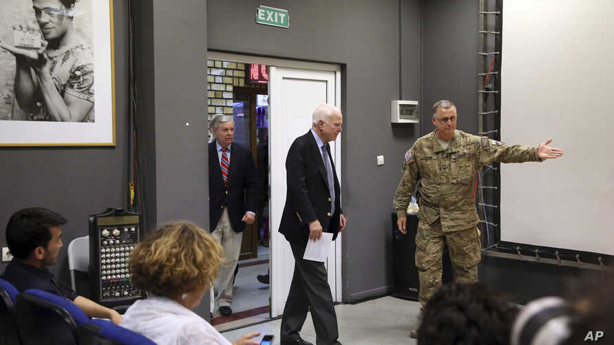 U.S. Senator John McCain, center, arrives for a press conference at the Resolute Support headquarters in Kabul, Afghanistan, July 4, 2017.
