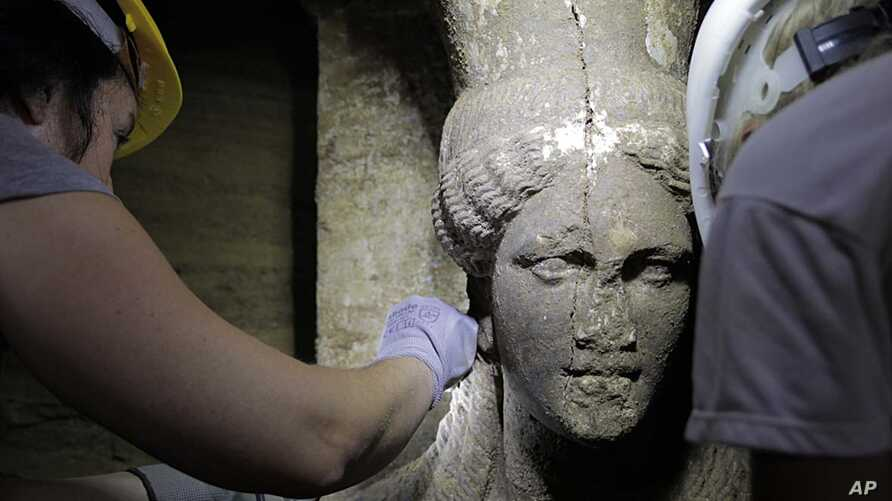 Archaeologists inspect a female figurine in a hall leading to an unexplored main room of an ancient tomb, in the town of Amphipolis, northern Greece, released by the Greek Culture Ministry, Sept. 7, 2014.