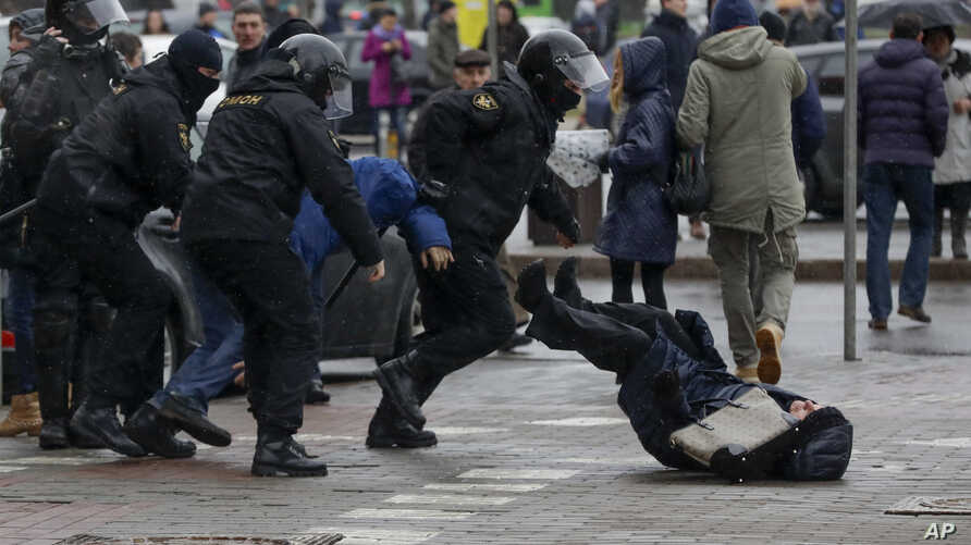 Belarus police push a woman down while detaining an activist during an opposition rally in Minsk, Belarus, March 25, 2017.