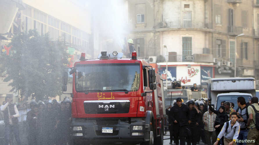 Egyptian riot police fire a water cannon to disperse people protesting against a new law restricting demonstrations, in downtown Cairo, Nov. 26, 2013.