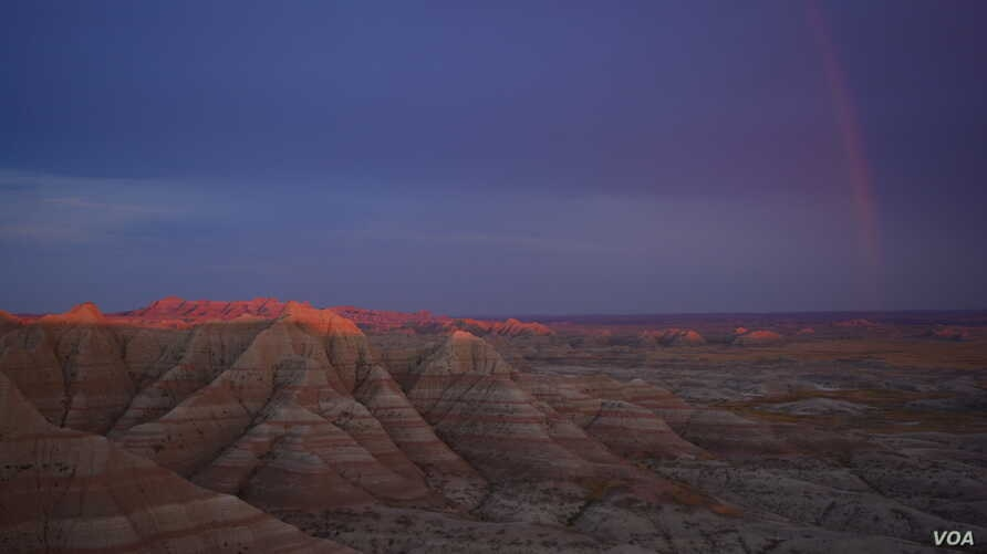 After a storm, a rainbow lights the rugged peaks of the Badlands National Park.