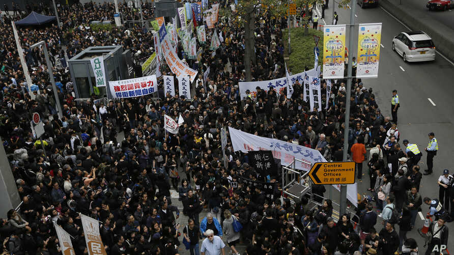 Journalists and their supporters gather outside government headquarters in Hong Kong, March 2, 2014, to protest the attack on a prominent former newspaper editor and to express support for freedom of the press.