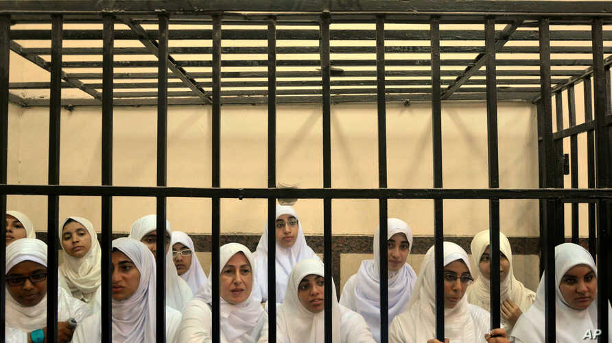 Egyptian women supporters of ousted President Mohamed Morsi stand inside the defendants' cage in a courtroom in Alexandria, Egypt, Nov. 27, 2013.