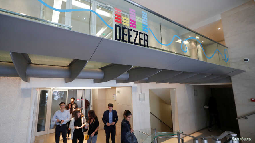 FILE - Employees pass under a logo at Deezer's headquarters in Paris, France, Sept. 5, 2017.