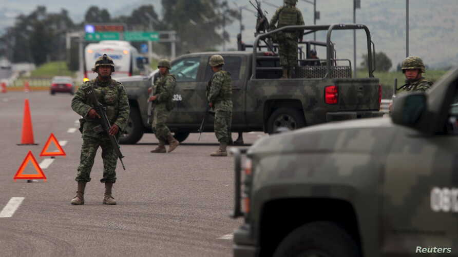 """Soldiers stand guard at a checkpoint near Contepec, in Michoacan state,  after Mexico's most notorious drug lord, Joaquin """"El Chapo"""" Guzman, broke out of a high-security prison Saturday for the second time, escaping in a tunnel built right under his"""