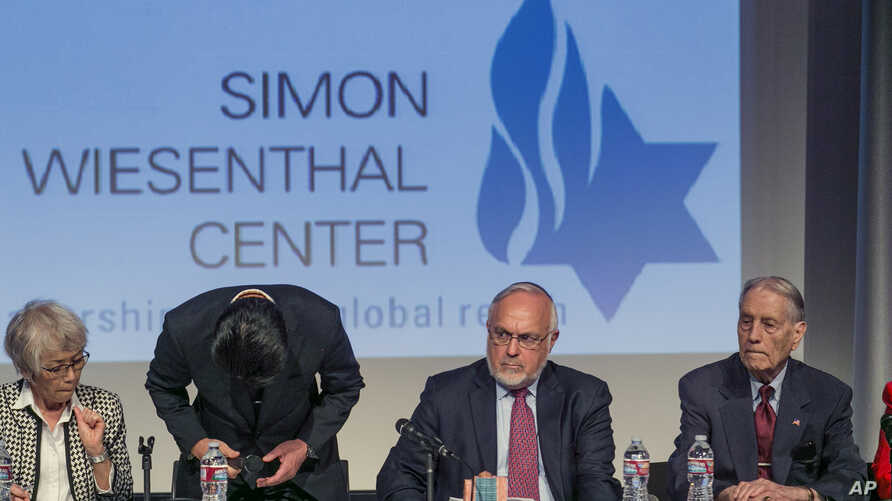 Hikaru Kimura, Senior Executive Officer of Mitsubishi Materials, bows down to offer an apology to 94-year-old James Murphy, a U.S. prisoner of war during World War II, far right, and relatives of other former POWs at the Simon Wiesenthal Center in Lo