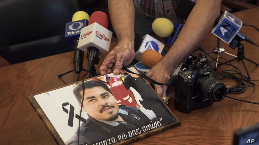 A member of the media displays an image of slain Mexican journalist Edgar Daniel Esqueda Castro, in protest, before the start of a press conference in San Luis Potosi, Mexico, Oct. 6, 2017.  The body of Esqueda Castro, a freelance photographer, was f