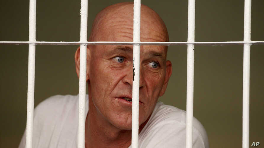 British national and former news correspondent David Fox inside his cell speaks to his lawyer after his trial in Bali, Indonesia, Jan. 19, 2017.