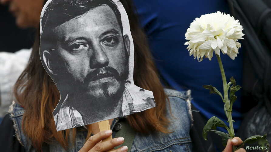 An activist holds up a picture of photojournalist Ruben Espinosa during a protest against his murder at the Angel of Independence monument in Mexico City, Mexico August 2, 2015.