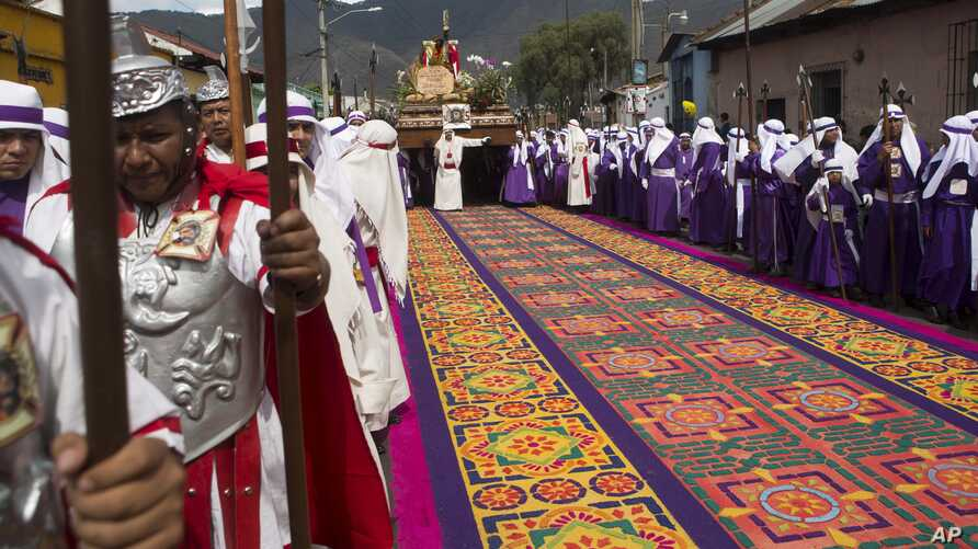 FILE - A street decoration made from dyed sawdust lays intact before a Good Friday procession walks over it during Holy Week in Antigua, Guatemala, Apr. 3, 2015.