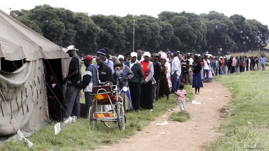 People queue to vote in a referendum at a polling station in Harare, March 16, 2013.
