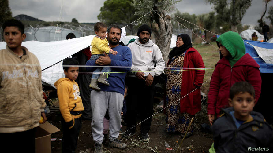 Syrian refugee Bashar Wakaa (3rd L) and his family stand in front of their tents at a makeshift camp for refugees and migrants next to the Moria camp on the island of Lesbos, Greece, Nov. 30, 2017.