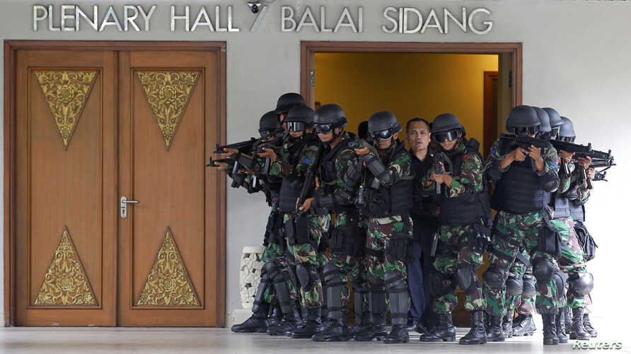 """FILE - Members of the Indonesian Security Force evacuate a """"VIP"""" during an anti-terror drill at Jakarta Convention Center."""