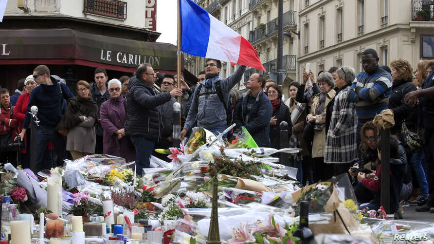 People pay tribute to victims outside Le Carillon restaurant