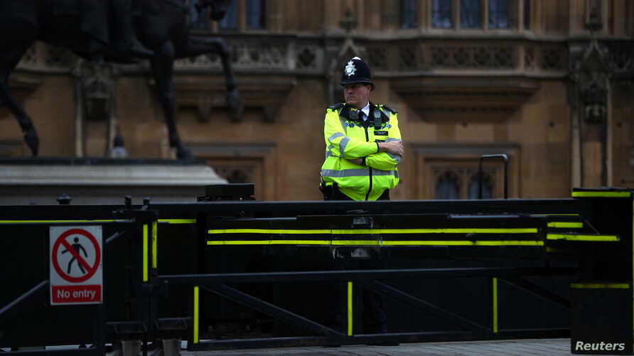 FILE - A police officer stands at a vehicle barrier at the Houses of Parliament, in Westminster, London, Britain, Aug. 15, 2018.