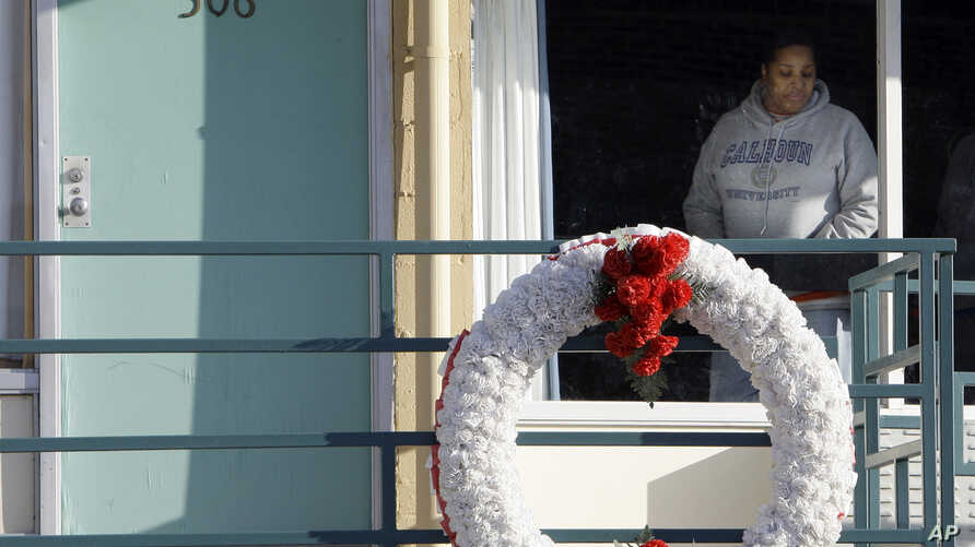 FILE - In Jan. 19, 2009, file photo, a woman looks out of a window while visiting the National Civil Rights Museum located at the Lorraine Motel in Memphis, Tenn., on the nationwide holiday honoring Martin Luther King Jr. The wreath marks the locatio