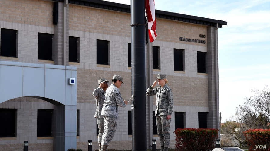 Members of a flag detail lower the flag in front of the Norma Brown Building on Goodfellow Air Force Base, Texas, March 16, 2018. (Airman 1st Class S. Hines / USAF)