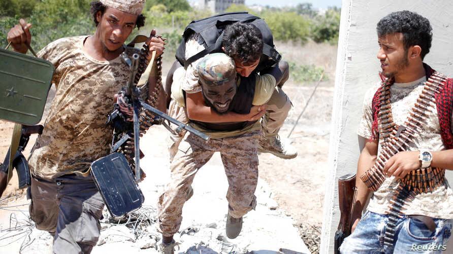 A fighter of Libyan forces allied with the U.N.-backed government runs for cover with another fighter while carrying a wounded fighter during a battle with Islamic State fighters in Sirte, Libya, July 31, 2016.