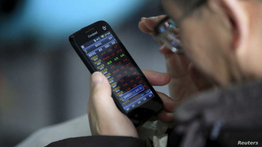 An investor checks stock information on a mobile phone at a brokerage house in Shanghai, China, March 7, 2016.