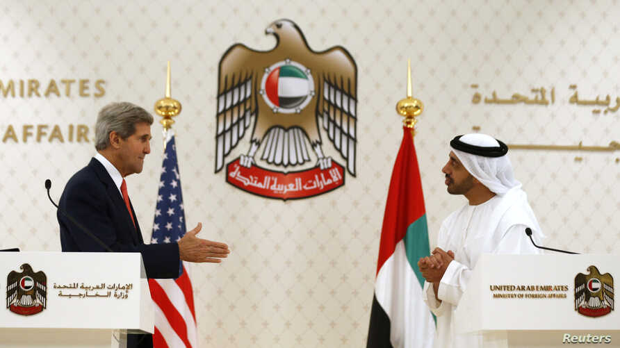 U.S. Secretary of State John Kerry (L) reaches out to shake hands with UAE Foreign Minister Abdullah bin Zayed Al Nahyan at the foreign ministry in Abu Dhabi, Nov. 11, 2013.