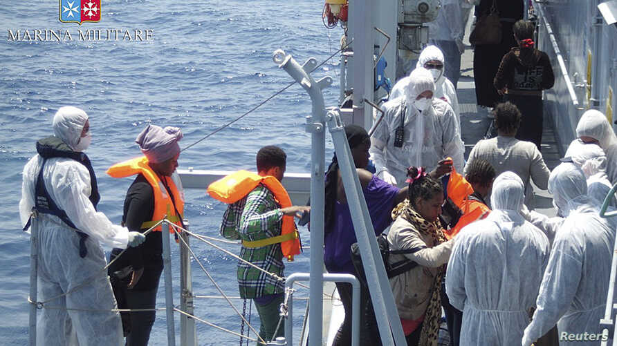 Migrants walk aboard the Italian navy ship Scirocco during a rescue operation about 40 nautical miles off the coast of Libya in this handout picture released on June 14, 2014 by the Italian Marina Militare.