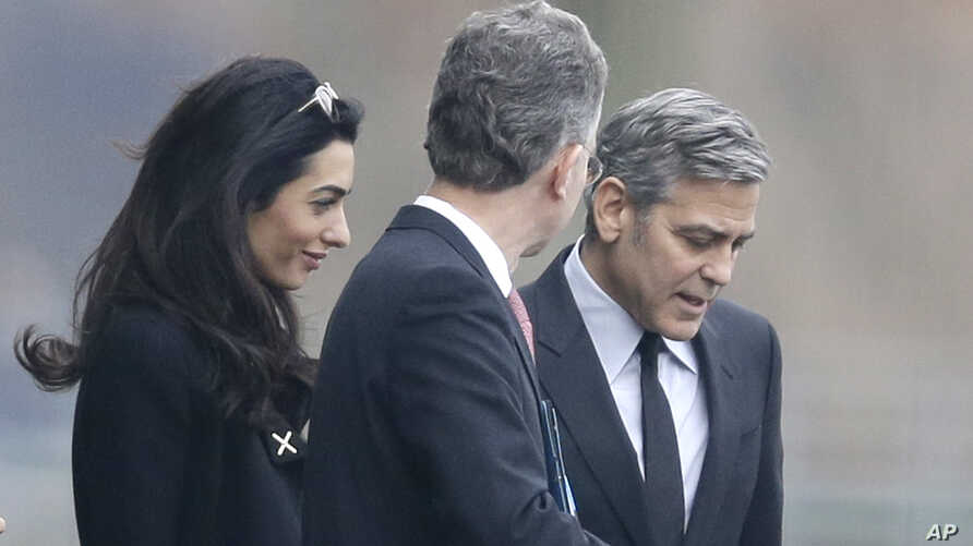 U.S. actor George Clooney, right, and his wife Amal Clooney, left, are accompanied by Merkel's foreign policy advisor Christoph Heusgen as they leave chancellery after private meeting with German chancellor Angela Merkel in Berlin, Germany, Feb. 12,