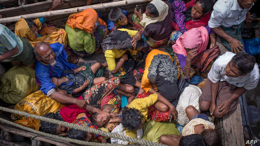 FILE - This photograph taken on Sept.12, 2017 shows Rohingya refugees arriving by boat at Shah Parir Dwip on the Bangladesh side of the Naf River after fleeing violence in Myanmar.