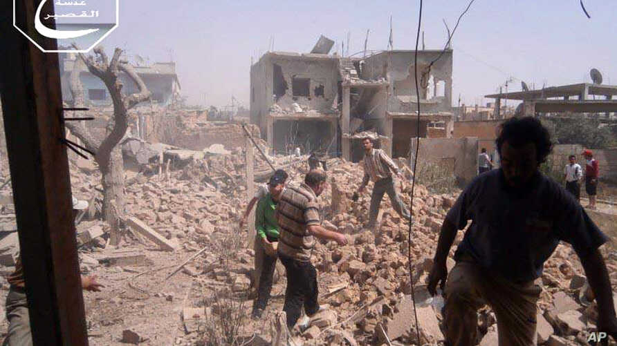 In this May 18, 2013 citizen journalism image provided by Qusair Lens which has been authenticated based on its contents and other AP reporting, shows Syrians inspecting the rubble of damaged buildings due to government airstrikes, in Qusair, Homs pr