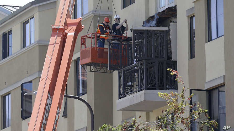 Workers with BELFOR Restoration Company look at a fourth floor balcony railing as it rests on the balcony below at the Library Gardens apartment complex in Berkeley, Calif. on Tuesday, June 16, 2015.