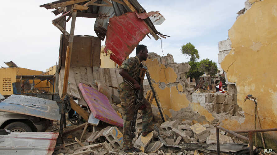 A Somali soldier stands near a destroyed building outside the police traffic station in Mogadishu, Somalia, Monday, May, 9, 2016.