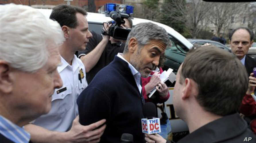 Actor George Clooney, center, and Rep. Jim Moran, D-Va., left, are led to a police vehicle after being arrested during a protest at the Sudan Embassy in Washington,  March 16, 2012.