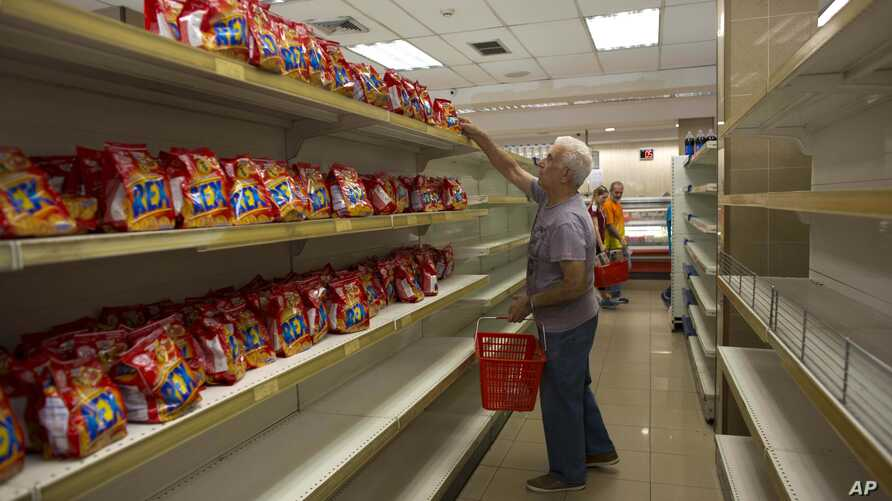 FILE - A man takes a package of cookies surrounded by empty shelves of a supermarket in Caracas, Venezuela, March 23, 2018.