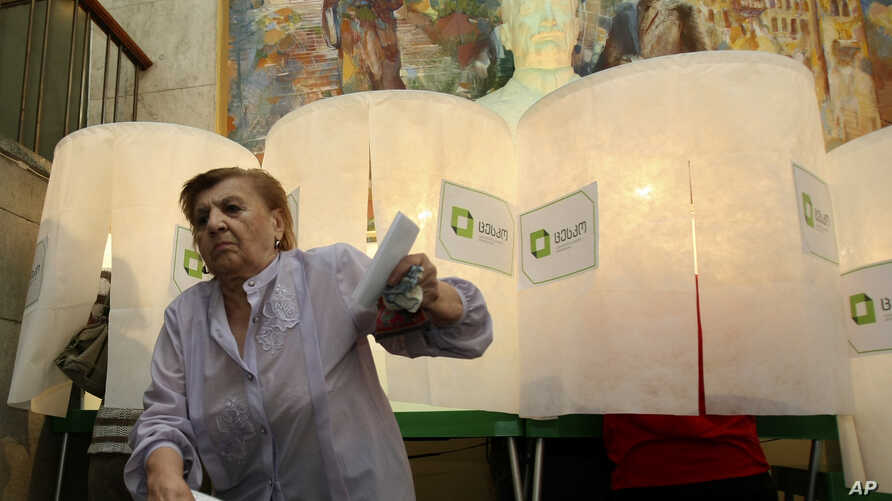 A woman leaves a voting booth at a polling station in Tbilisi, Georgia, Oct. 1, 2012.