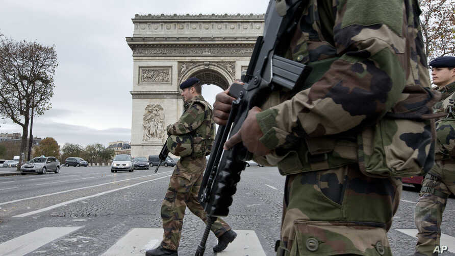 French soldiers cross the Champs Elysees avenue passing the Arc de Triomphe in Paris, Nov. 16, 2015.
