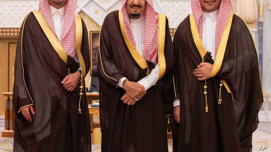 In this photo provided by the Saudi Press Agency, the new Economy and Planning Minister, Mohammad al-Tuwaijri, right and the new National Guard chief, Prince Khalid bin Ayyaf al-Muqrin, left, pose for a photo with King Salman during a swearing in cer