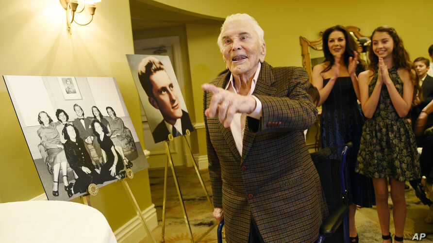 Actor Kirk Douglas arrives at his 100th birthday party as his daughter-in-law Catherine Zeta-Jones (second from right) and her daughter Carys applaud at the Beverly Hills Hotel, Dec. 9. 2016, in Beverly Hills, Calif.