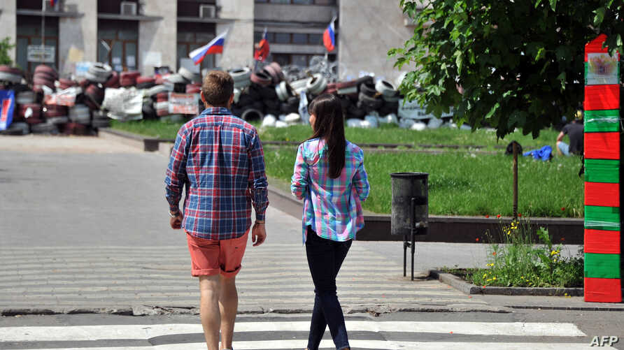 A young couple walks near a barricade outside the regional administration building in Ukraine's eastern city of Donetsk on May 14, 2014.