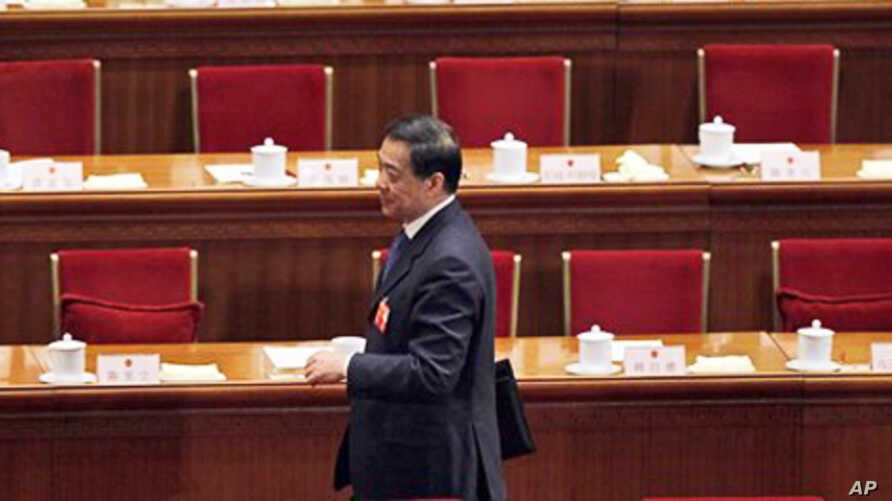 Bo Xilai walks past deserted seats after a plenary session of the National People's Congress in Beijing, China, March 9, 2012.