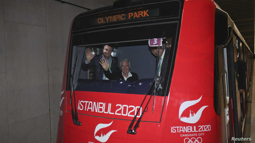 International Olympic Committee (IOC) Vice President and chairman of the IOC Evaluation Commission Craig Reedie (2nd L), and Hasan Arat, leader of the Istanbul 2020 Bid Committee (L), wave from a metro train in Istanbul Mar. 24, 2013.