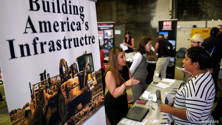 A recruiter talks with a job seeker at the Construction Careers Now! hiring event in Denver, Colorado, Aug. 2, 2017.