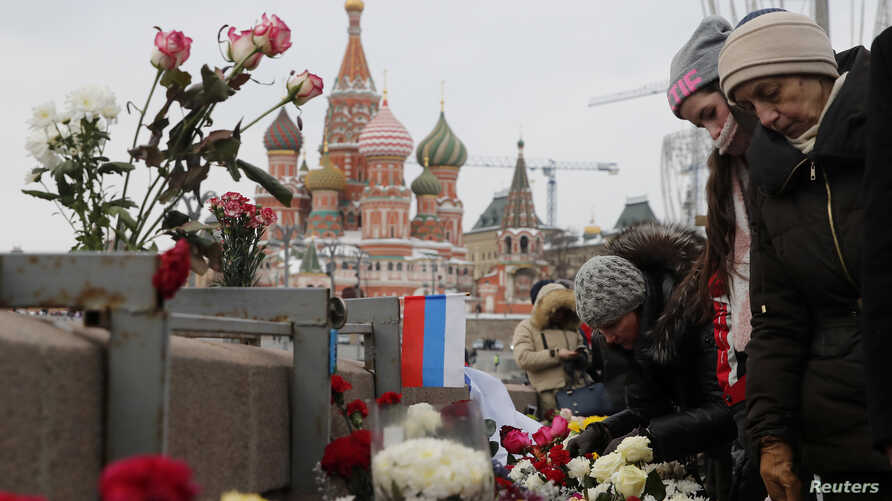 People visit the site of the assassination of Russian opposition leader Boris Nemtsov as they mark the third anniversary of Nemtsov's death, with the St. Basil's Cathedral seen in the background, in central Moscow, Russia Feb. 25, 2018.