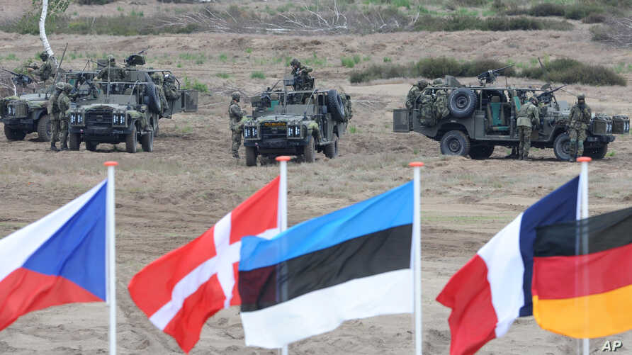 Flags wave in front of soldiers taking positions with their army vehicles during the NATO Noble Jump exercise on a training range near Swietoszow Zagan, Poland, June 18, 2015.