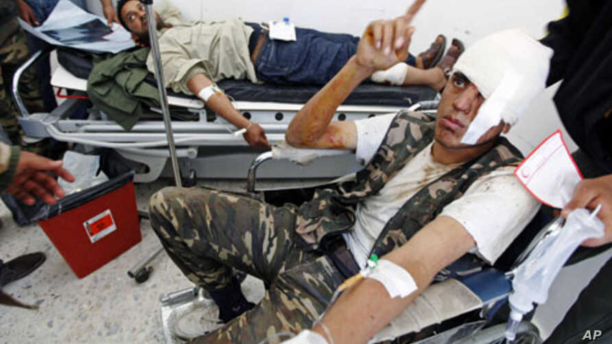 Wounded rebel fighters are treated in a hospital in Ajdabiyah after being brought in from the road to Ras Lanuf, in Libya, March 30, 2011